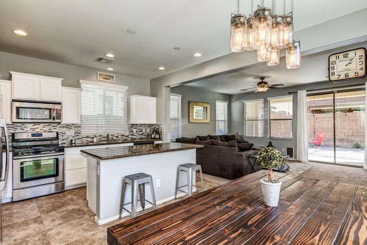 Staggered White Cabinets, Granite Countertops, Large Island, Recessed Lighting, Under Mount Lighting, Stainless Steel Appliances, Gas Range, Refrigerator Included, Upgraded Lighting in Dining Area, Neutral Two Tone Paint, Tile Flooring