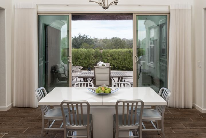 Centered sliding doors open to the patio with open skies, a view of Pinnacle Peak and no neighbors to the north. Custom window treatments including plantation shutters are detailed through out this home.