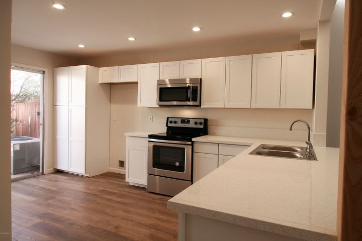 New white shaker-style cabinets, quartz counter tops, and new stainless appliances.