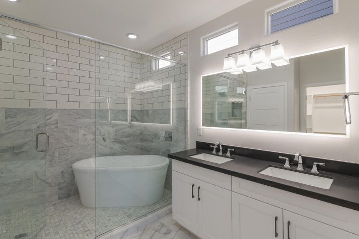 The master bathroom features a glamorous soaking tub inside the walk-in shower with a full-glass shower door & double vanity with lighted mirror