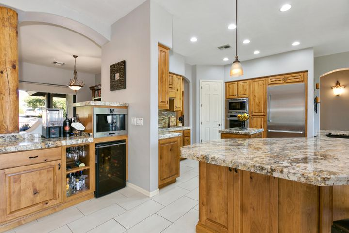Gourmet Kitchen with knotty alder cabinets, slab granite, built-in fridge, double ovens and microwave.