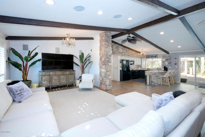 Open floor plan with wood beamed ceilings and surround sound