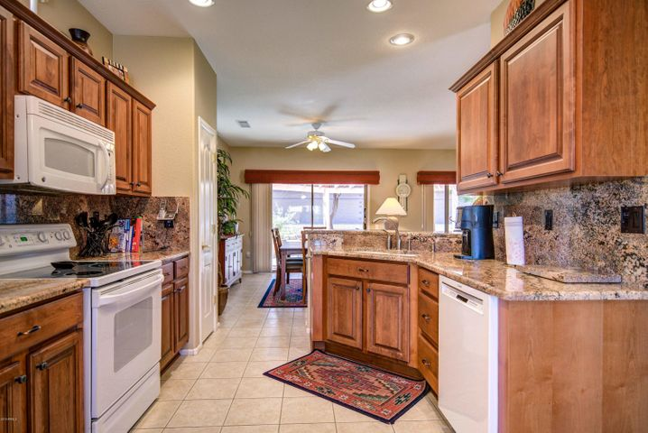 Beautiful kitchen with refinished cabinets, granite countertops and splash back