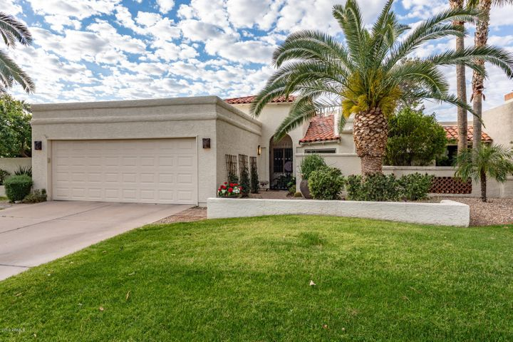 Great curb appeal, with gorgeous palm treees, lush greenery, and beautiful custom iron gates.