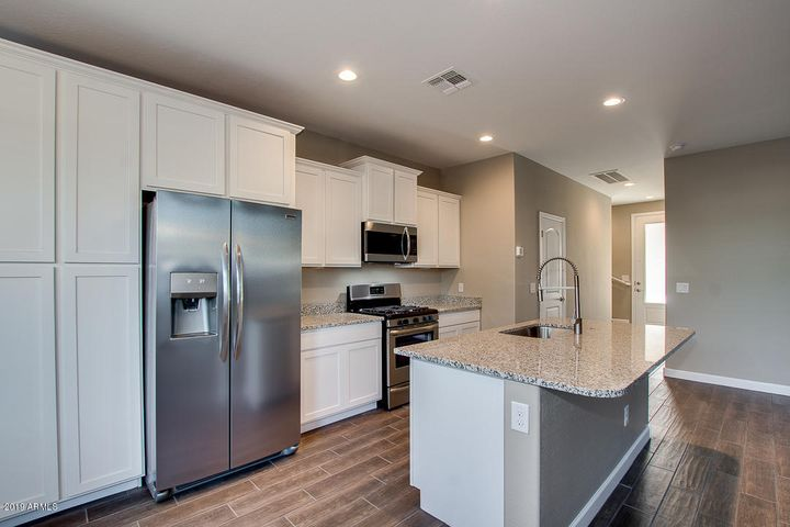 Gorgeous kitchen with designer White Shaker Cabinets and granite countertops. Photos represent same floorplan and interior package.