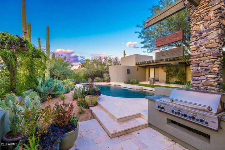 Outdoor kitchen sits off the pool area.
