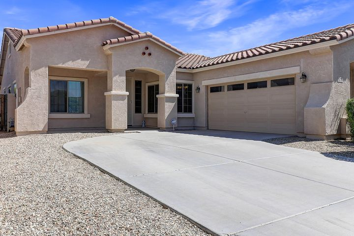 Front of home with large driveway.