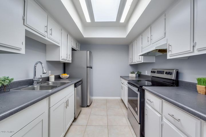Kitchen with white cabinets & stainless steel appliances
