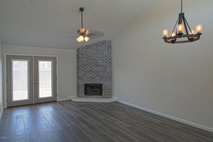 Beautiful brick fireplace (pre-wired for a flat panel TV behind the brick) Ceiling fan and dining area chandelier provide a warm ambience.