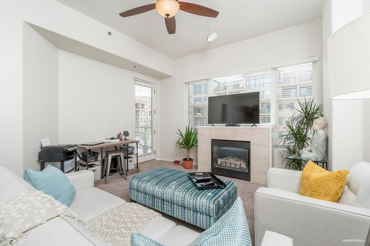 Open and bright living room with built-in gas fireplace and door out to spacious balcony.