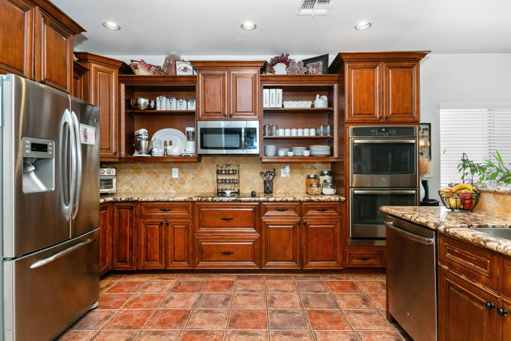 Kitchen with Cherry Cabinets, Slab Granite Counters, Stainless, Electric Cooktop, Wall Ovens, Dishwasher and Microwave