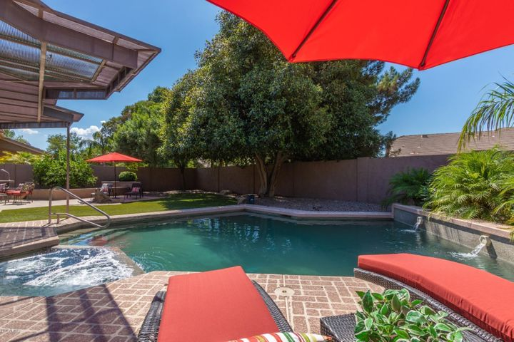 Resort backyard living! Huge heated pool with water feature and a relaxing spa! Lock and leave with artificial turf!