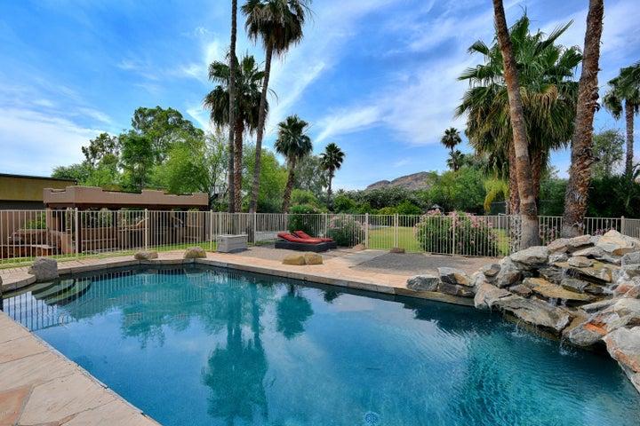 Beautiful pool with rock waterfall and sandy beach area.