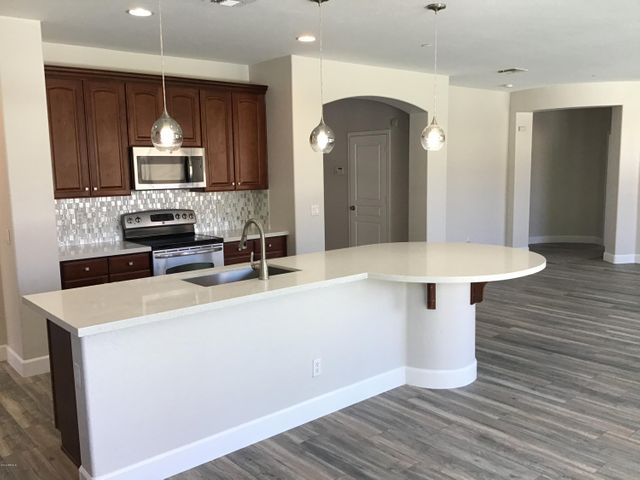 Huge kitchen island with Quartz counters and cherry cabs