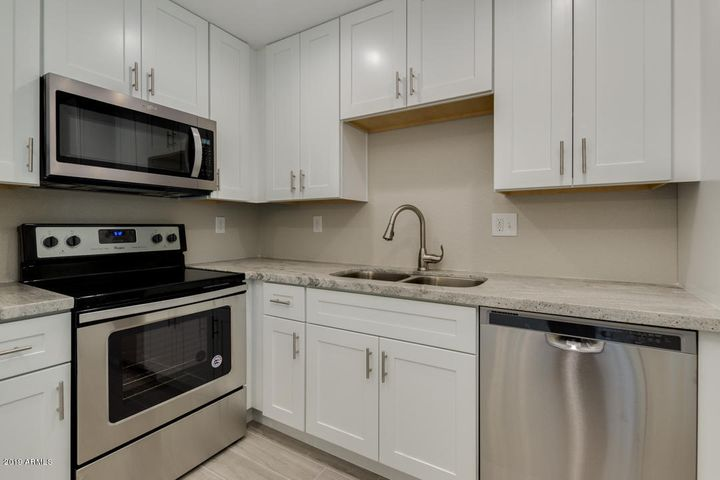Beautiful kitchen with shaker-styled cabinets, granite countertops, new stainless steel appliances, & more!