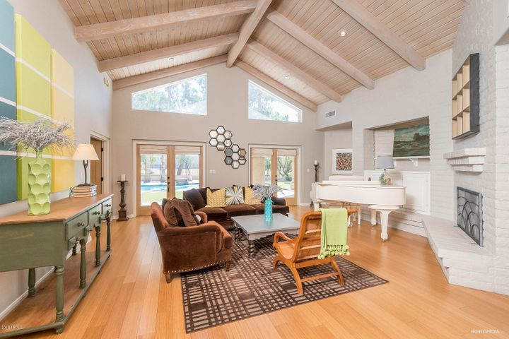Living room features french doors leading out to the sparkling pool