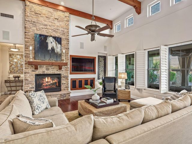 Family room overlooks the backyard and mountain views. Relax in this spacious setting while enjoying the gas stacked stone fireplace. The wood beams add architectural appeal.
