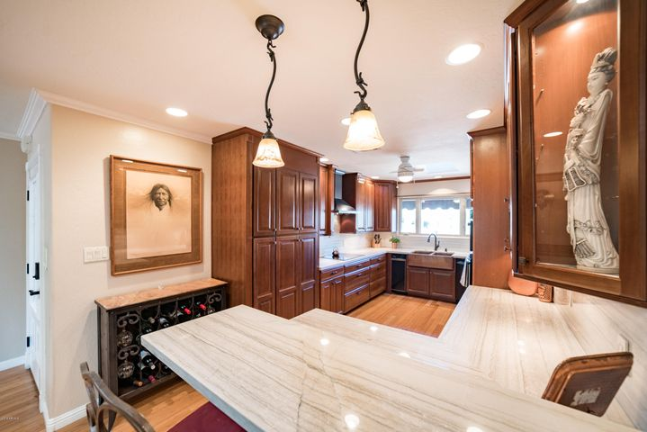Stunning Quartzite countertops, custom cherry cabinets, induction range, custom range hood, pot filler, wall oven, micro/convection oven, custom lighting, trash compactor, wine fridge, breakfast bar and a walk-in pantry.