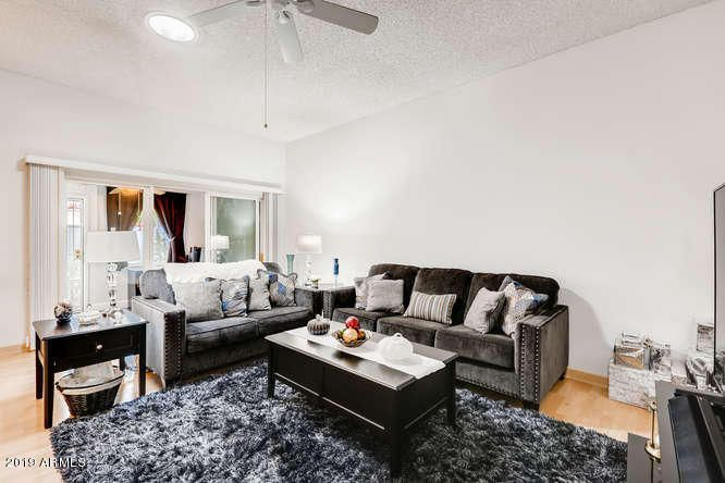 Living room with ceiling fan and solar tube.