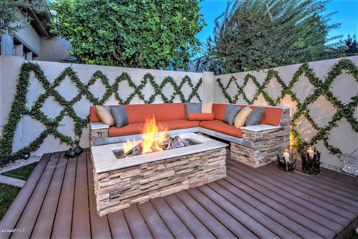 Raised Gas Firepit with matching stacked rock bench seating. Living ivy trellis background.