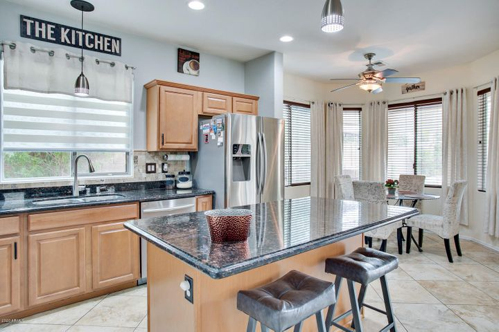 Spacious kitchen with dark granite counters, contrasting light cabinetry.