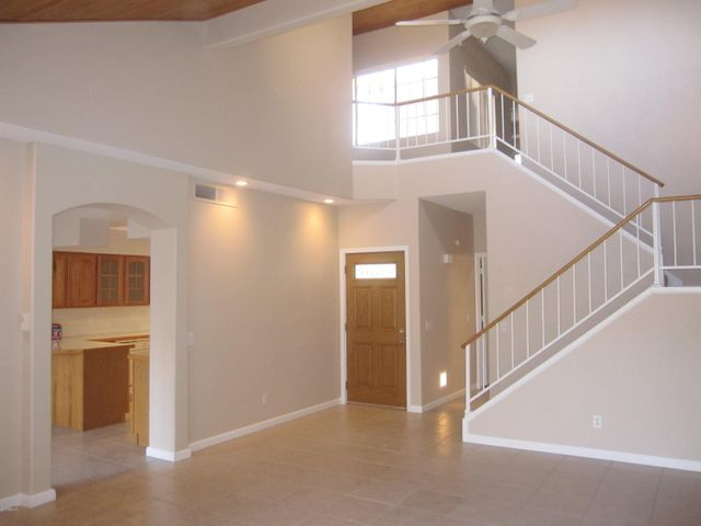 Lots of impact with two-story LR with wood ceiling. View into Kitchen/Family Room.
