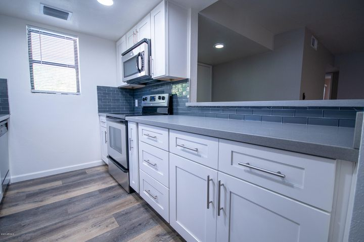 Grey Quartz Counter-tops, Stainless Steel Appliances, White Cabinets, Wood Laminate Floors, Fresh 2 - tone paint.