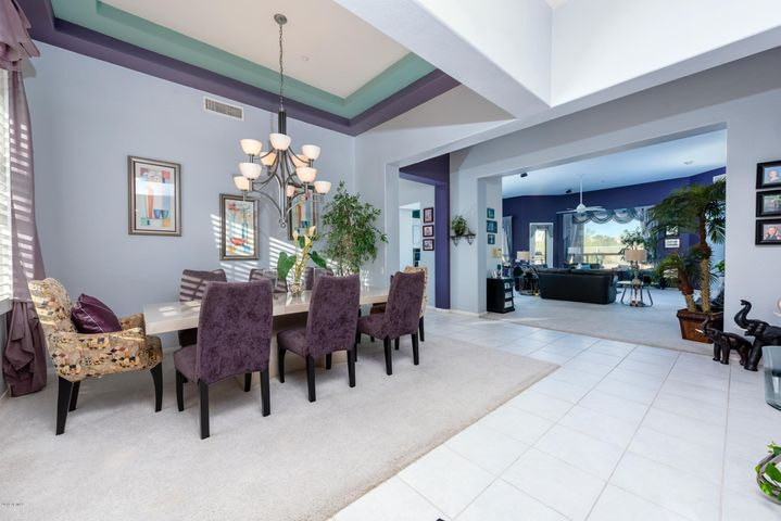 View of home from entrance, elegant formal dinning room with coffered ceiling and grand chandler ($2500).