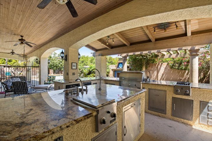 Complete outdoor kitchen with granite counters, natural gas grill & cooktops, mini refrigerator and dishwasher