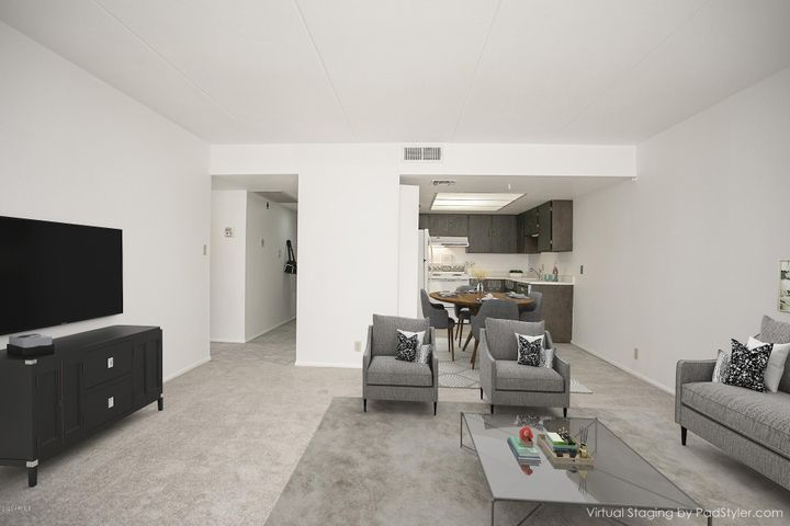 Virtually staged living space with room for dining set.