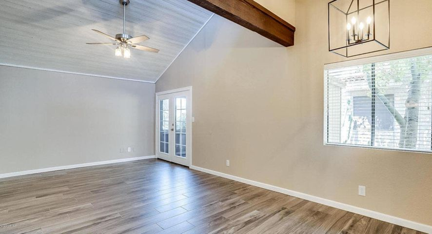 Great Room with vaulted/beamed ceiling! Wood look tiled flooring throughout the home.