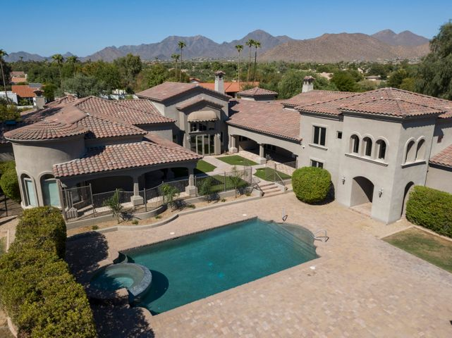 Impressive aerial view of rear of home and the McDowell Mountains in the distance