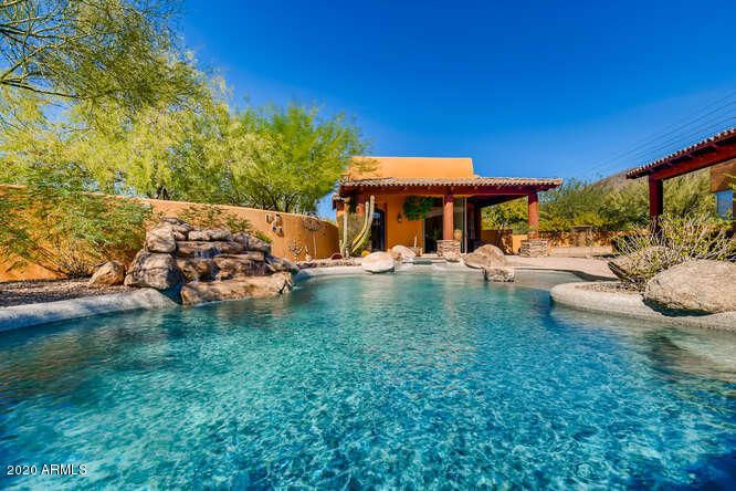 Both residences wrap around sparkling pool with boulder waterfall, bubbling heated spa, adjacent grassy side yard with majestic water fall and Mountain Views Carefree is known for