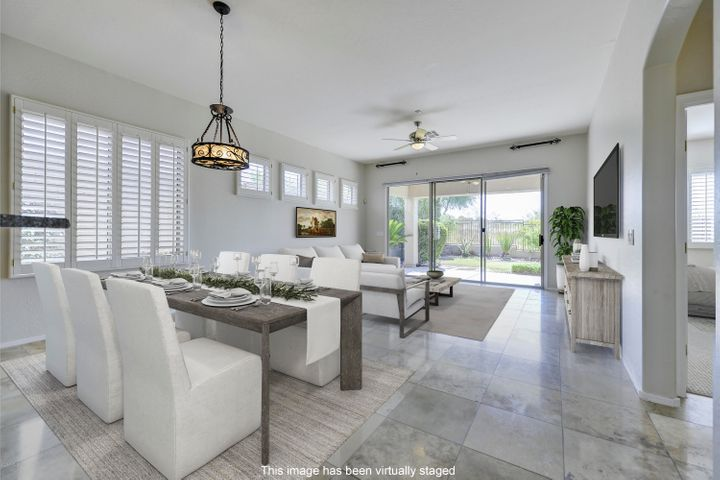Draped in natural light, travertine flooring, plantation shutters and a triple panel sliding door, the great room draws the beauty of the outside in.