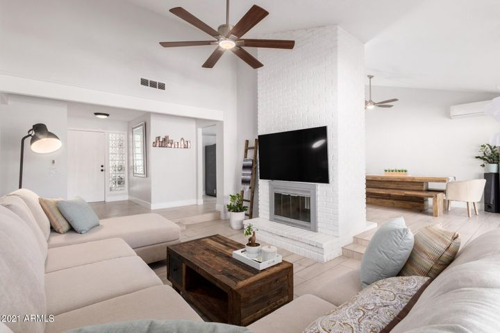 Large living room, entry way and dual fireplace into kitchen.