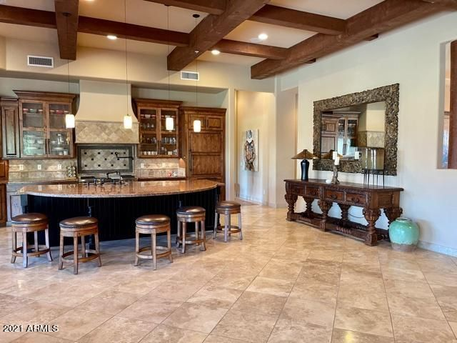 Spacious great room floor plan with travertine flooring and beams. And Alder custom Cabinetry with handsome handles. All lower cabinets with roll out drawers.