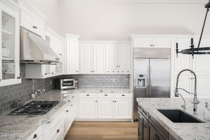 Six burner gas cook top, wall oven & microwave, Asko dishwasher, under the counter SubZero wine fridge, r/o, Blanco sink with Kohler chrome and black faucet, granite countertops, detailed with a zinc colored backsplash that has a subtle shimmer in the evening light.