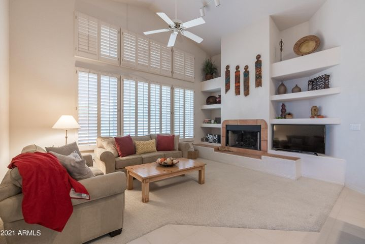 Cozy family room with fireplace and lots of shuttered windows