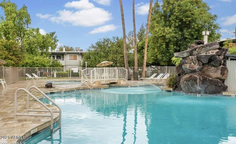 Gorgeous community pool with waterfall and fenced