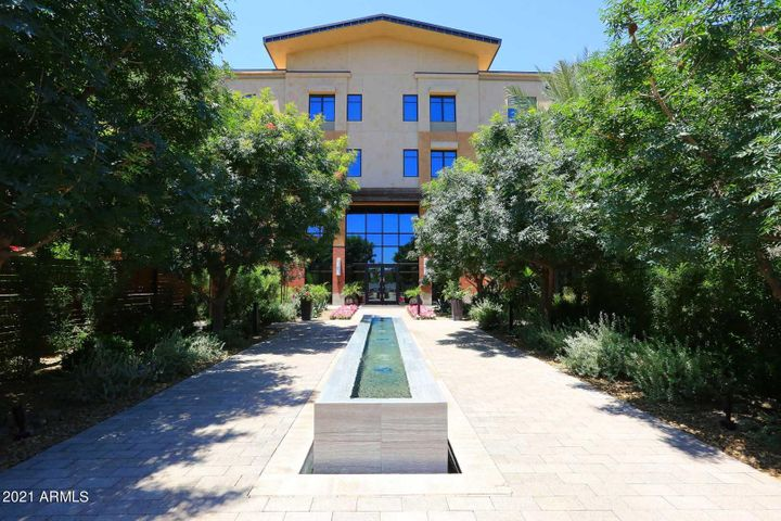 As you walk to the entrance of the building, there is a long negative edge fountain and lush landscape to greet you.