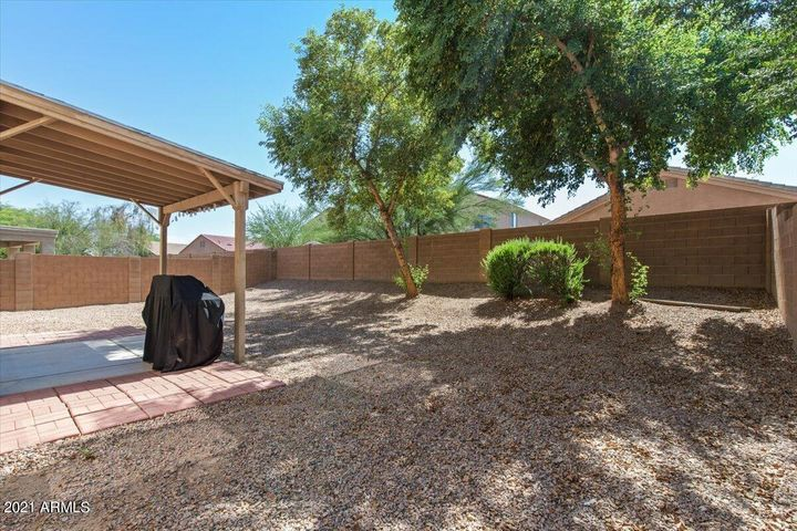 Low maintenance backyard with gravel, bushes, a tree, and a Pergola.