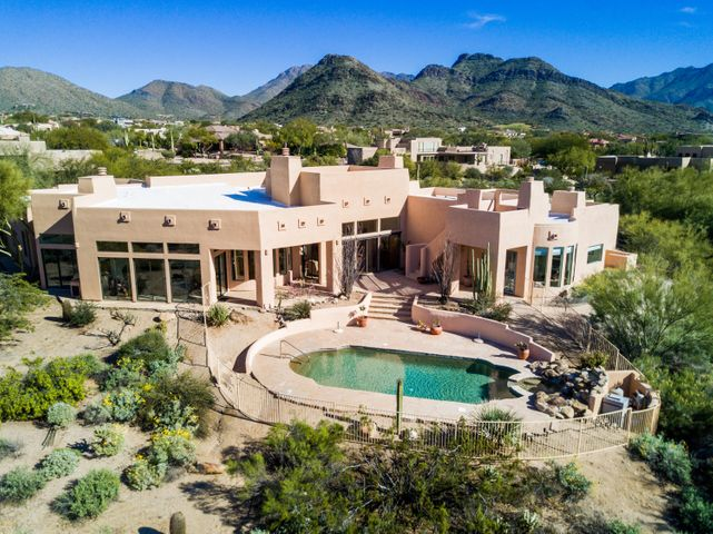 Stunning, secluded SW contemporary custom home on 1.3 acres in Pinnacle Peak Vistas. This home offers privacy, dramatic views including a legally-protected SW view corridor, open floor plan, custom stone flooring, multiple fireplaces, large windows allowing for plenty of natural lighting, and much more! Upon entering through a private courtyard, the great room features high coffered ceilings, a two-way wood burning fireplace, and expansive backyard views. Off the great room is the formal dining room. The gourmet kitchen is white and bright and boasts granite counter tops, oversized stainless steel refrigerator, wine refrigerator, island with separate produce sink, wall oven, 72 sqft walk-in pantry, and enormous breakfast bar. Open to the kitchen are the breakfast room and family room, each with its own fireplace. The spacious master suite features a sitting area with three-way fireplace, double vanities, jetted tub, separate oversized shower, granite counter tops, and 2 walk-in closets. Two secondary bedrooms are down a separate hall with a full bath. A 4th bedroom and full bath on the opposite side of the home is perfect for guests and a 5th bedroom with cozy fireplace, currently configured as an office, is off the living room. The oversized laundry room and the 4-car garage complete this home. Entertain in the backyard under the covered patio, in the sparkling pebble-tec pool and spa with boulder waterfall feature, or on the 2nd story roof view deck sitting by the exterior fireplace enjoying panoramic city, desert, and mountain views. The property has plenty of space for additions, extra garages, RV storage, play area, or patio expansion. With the upgrades and ultimate privacy and views, what more do you need? Schedule your showing today!