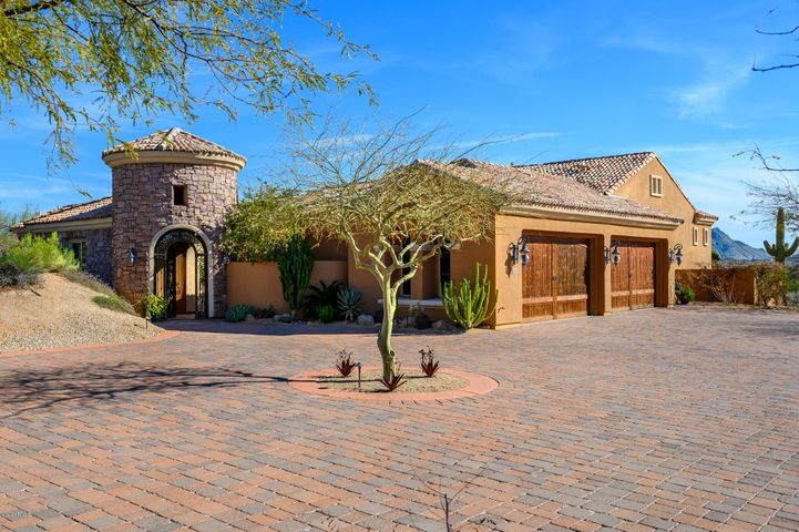 This stunning custom home in gated Troon Verde features a 3BR/2.5BA main house & 1BR/1BA detached casita, all connected by an enclosed outdoor courtyard with water feature & gas fireplace. Nestled on a 1.687 acre corner lot with protected, sweeping views of the McDowells & Pinnacle Peak, this home seamlessly blends indoor & outdoor living at every turn. Main home features a split floorplan centered around a lg. great room with an arched, brick ceiling, custom stonework, & retractable wall of glass. Chef's kitchen is appointed with Viking appliances, Subzero refrigerator/freezer, copper farm sink & oversized island. Stone floors & custom Alder cabinetry throughout. Backyard oasis boasts a covered patio, negative edge pool, spa, swim up bar & built-in BBQ. Arizona living at its finest!