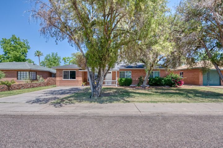 This updated brick charmer is located in a flourishing area just around the corner from Los Olivos Park, Sprouts, Wandering Tortoise, Noble Eatery, Town & Country Shopping Center, and Biltmore Fashion Park. The open interior floor plan features a spacious living room that flows into the formal dining area and remodeled kitchen, complete with quartz counter tops, shaker style cabinetry, stainless steel appliances, and a breakfast bar. Clean grays and whites accent the home with wood-look laminate flooring throughout. Mature trees line the property and the expansive backyard offers endless possibilities. Enjoy no HOA fees and the newer roof for years to come!