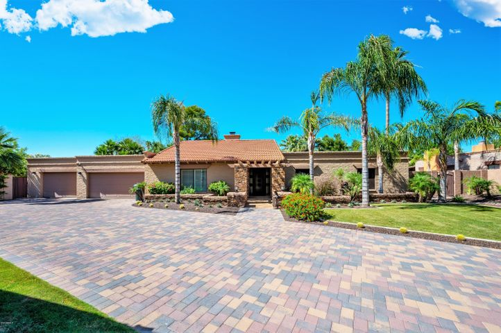 CHECK OUT THE 3D TOUR! This stunning, turn-key home is tucked away in the highly-coveted Taliverde community in the Biltmore. The open, airy interior concept features vaulted ceilings, porcelain tile and a striking two-way fireplace that separates the formal living area and family room. The updated kitchen offers granite counters, custom cabinetry, Frigidaire Professional Series appliances and a spacious breakfast bar. In addition to a large master suite and two guest rooms with private en-suites, the owners added a 400 sq.ft. wing that makes for the perfect home office, gym, or theater. The backyard is an entertainer's paradise, complete with ample covered patio space, a sparkling pool and peaceful water feature. The 3 car garage with oversized bay provides plenty of parking and storage.