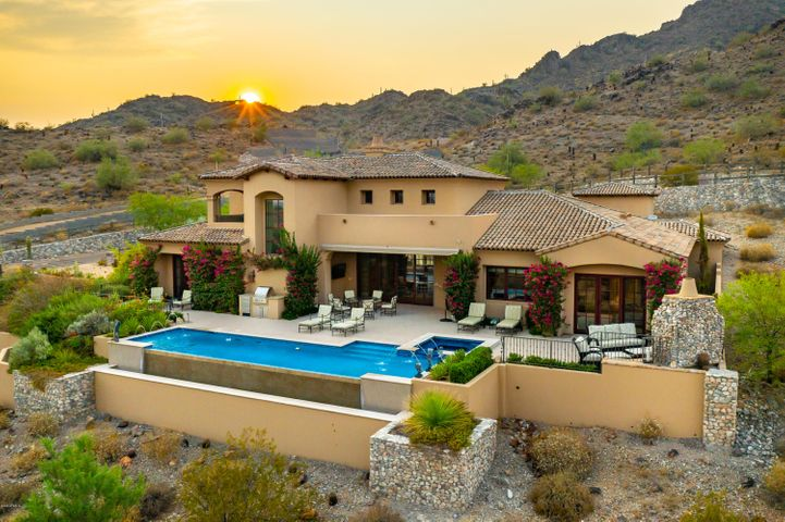 This custom luxury residence, built in 2013 by Cullum Homes, offers amazing Camelback Mountain Views with the master bedroom on the main floor! Just reduced by $500,000, what an incredible price. The over sized three-car air-controlled garage, allows room for your priceless toys! Home features DuChateau oak wood floors. The open concept features soaring wood-beamed ceilings and clerestory windows, while the gourmet kitchen is adorned with custom cabinetry,  granite center island, and Wolf/SubZero appliances. The bedrooms, kitchen and formal living room are on the main floor, while the second level features a spacious lounge/family room with an over-sized patio looking out to Camelback Mountain. The master retreat is the ideal sanctuary with a impressive en-suite, complete with a soaking tub, marble slab shower, dual vanities with light-up counter, and a walk-in closet fit for royalty. Outside, enjoy your infinity-edge pool, spa, outdoor fireplace, built-in grill, and stunning mountain views. The list of amenities and delights is endless with this home, so call today for your private showing!