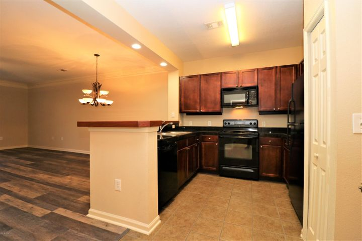 Spacious open kitchen with pantry to the right, dining and living area to the left