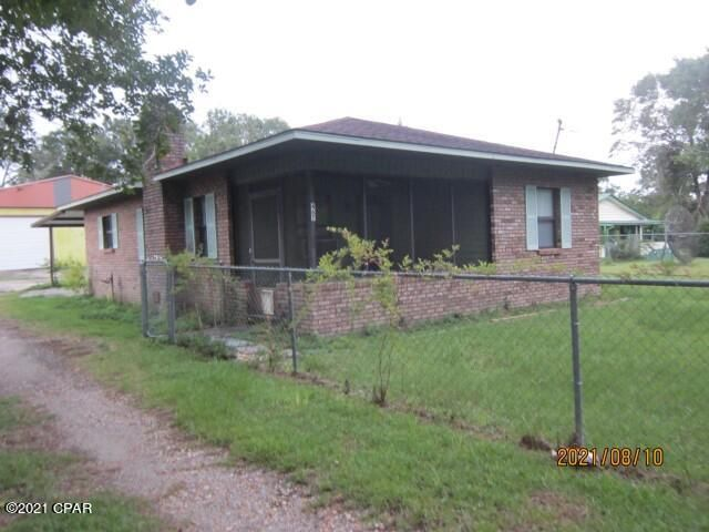 Front from driveway, showing chainlink fence around property.