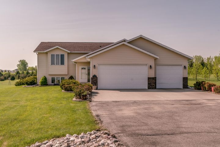 COUNTRY LIVING on 3 ACRES in a desirable location on PAVED ROADS less than 10 minutes from downtown Bismarck! This immaculate split level home features an OPEN CONCEPT kitchen, living and dining room great for entertaining.  Just off the kitchen you will find a LARGE PANTRY perfect for everything you need for family dinners! The main floor also has a LARGE MASTER bedroom with a master bathroom and a second bedroom and another full bathroom.  Downstairs you will find a WALKOUT BASEMENT with a family room with a GAS FIREPLACE another full bathroom, two more bedrooms, the laundry room and storage with built-in shelving.  The attached triple garage is heated and has a floor drain and H/C water and a doggy door with access to an outdoor kennel.  There is also a detached 30 X 35 SHOP with a concrete floor and 200V electric service.  There is a large garden plot ready for you to start planting your favorite vegetables.  The rear of the property is lined with mature trees.  Call today!