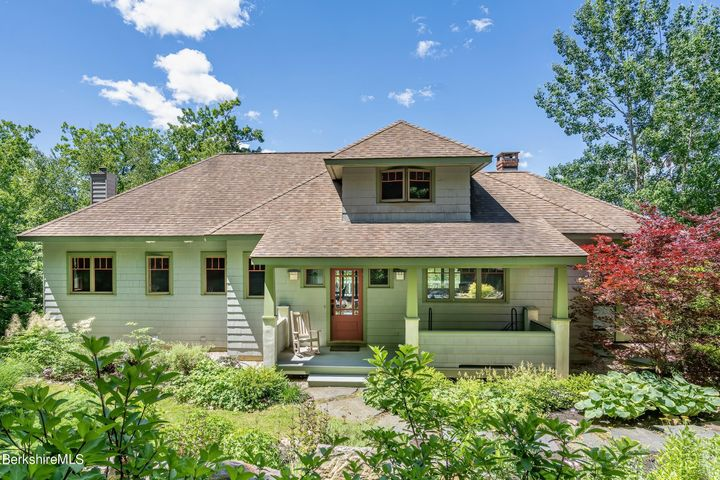 Classic Craftsman architecture with a welcoming front entry porch and lush perennial gardens.